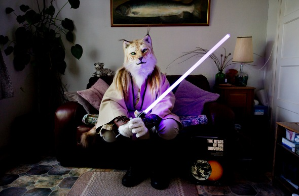 "Fangorn, a Jedi tiger sits in his living room, Swansea From the series"" At Home With The Furries"" Throughout the year furries dress up in costume or fur-suit inspired by anthropomorphic characters from cartoons, comic strips, myths and videogames. The people inside the suits are by day computer programmers, engineers, mortgage brokers, lecturers even fursuit makers. Most furries have an affinity with animals but some also like to role-play or fursuit for fun. Over the course of a few years, I gained the trust of the furries in the UK and some of their members allowed me to visit them at home, these photographs were taken all over the country. Contact tom@tombroadbent.com for licensing rights"